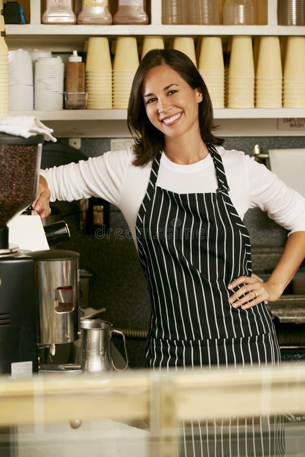 做咖啡的妇女在商店 免版税库存图片