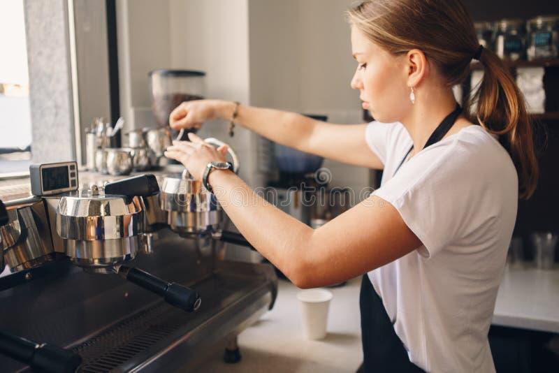 做咖啡的妇女barista在商店 库存图片