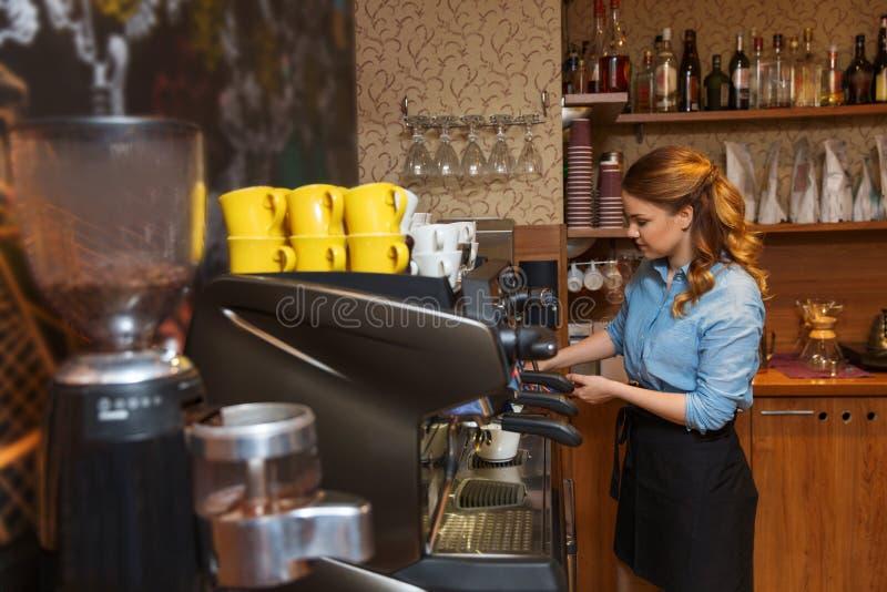 做咖啡的Barista妇女由机器在咖啡馆 免版税库存照片