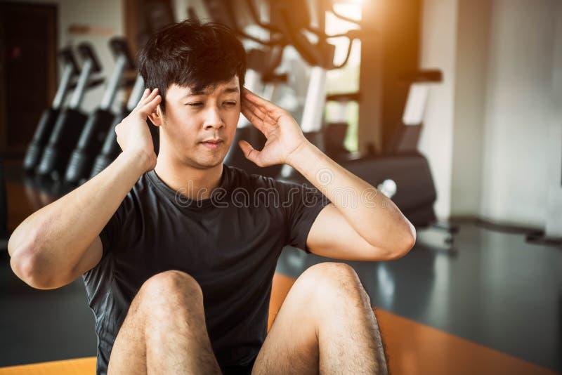 做咬嚼的亚裔体育人或姿势坐在健身健身房的瑜伽席子在公寓有健身房设备背景 E 免版税库存图片