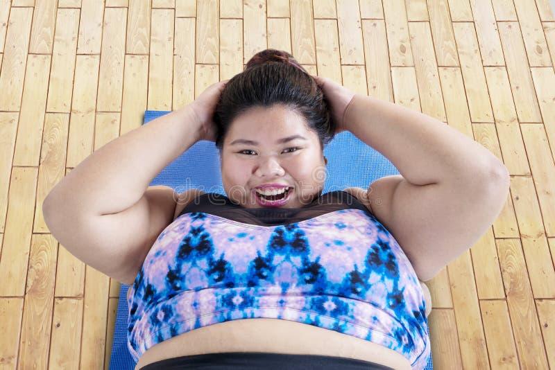 做咬嚼锻炼的愉快的肥胖妇女 免版税库存照片