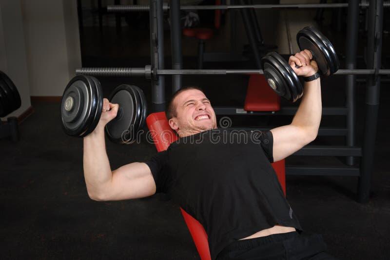 做哑铃在健身房的年轻人斜板推锻炼 免版税库存照片