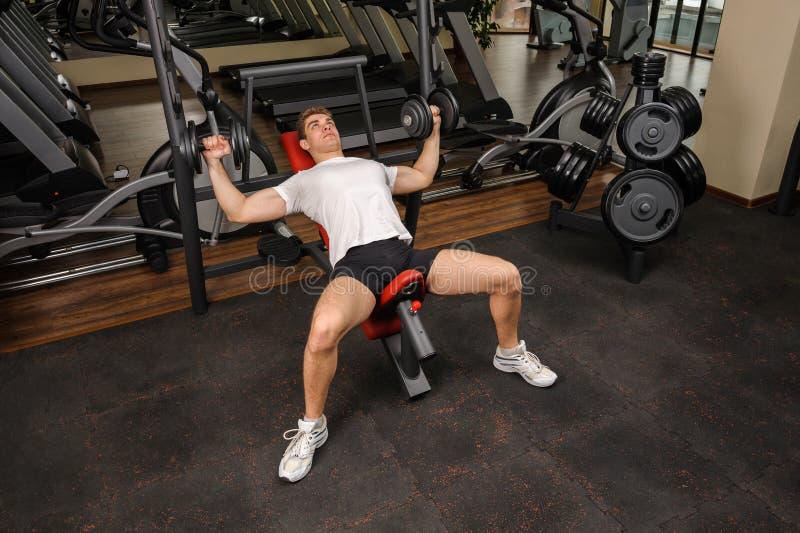 做哑铃在健身房的年轻人斜板推锻炼 库存照片