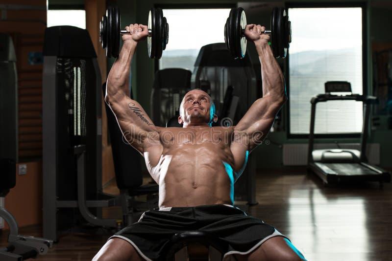 做哑铃斜板推锻炼的人 库存图片