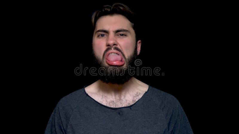 做嘴的情感和有胡子的年轻英俊的深色的人,伸出设法他的舌头戏弄 年轻有胡子 图库摄影