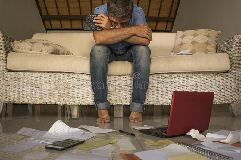 做国内认为的被淹没的和担心的痛苦经济的沮丧的人在家客厅长沙发越过 免版税库存照片