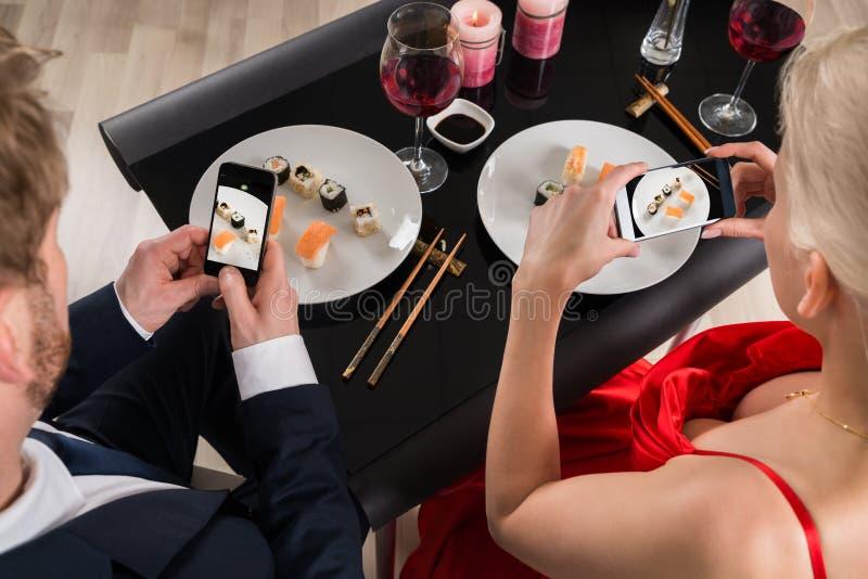 做图片的夫妇与他们的智能手机的食物 免版税库存图片