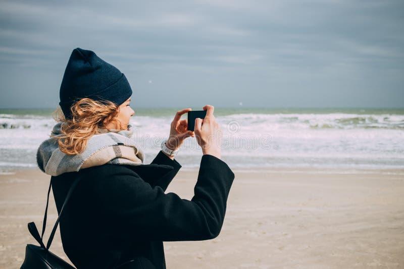 做图片的愉快的少妇旅客海滨 免版税库存图片