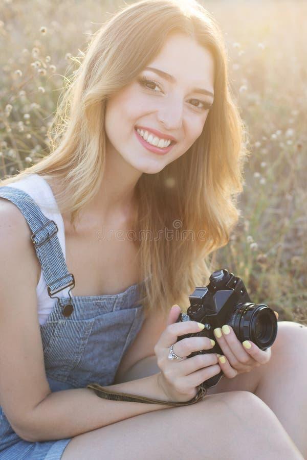 做图片的愉快的微笑的女孩由影片照相机 免版税库存照片