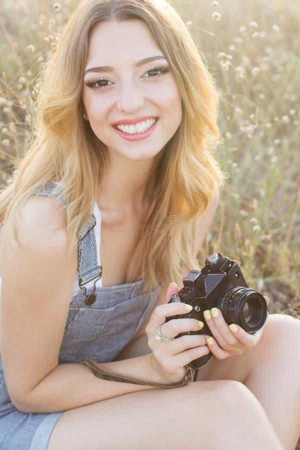 做图片的愉快的微笑的女孩由照相机 免版税库存照片