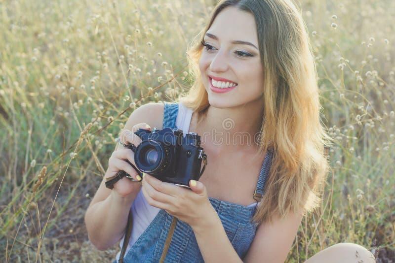 做图片的愉快的微笑的女孩由老照相机 免版税库存图片