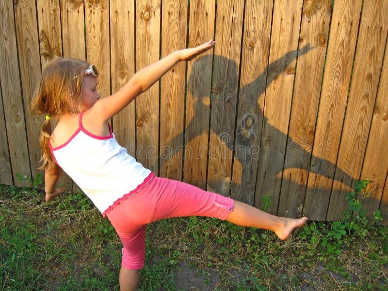 做图由阴影在木篱芭背景的女孩 免版税图库摄影