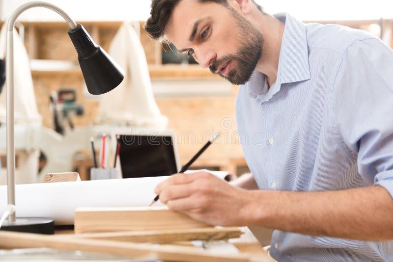 做图画的严肃的有胡子的木工在木材片断在工作场所 免版税库存照片