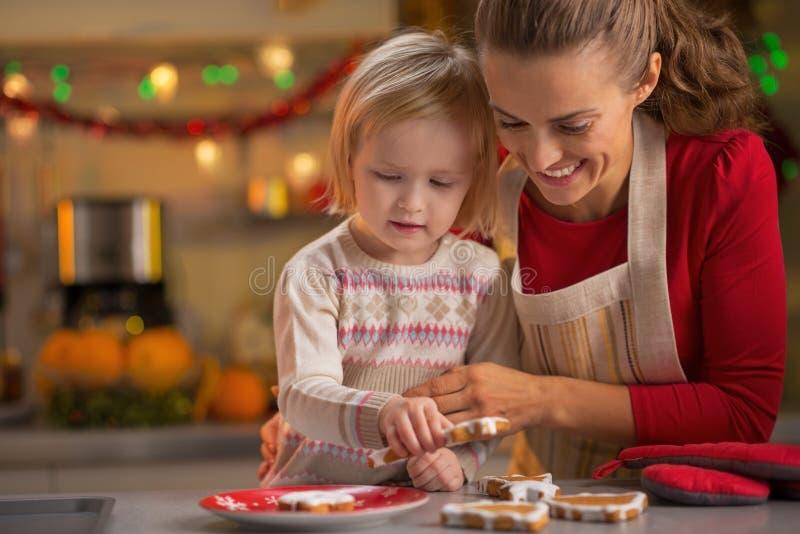 做圣诞节曲奇饼的微笑的母亲和婴孩 图库摄影