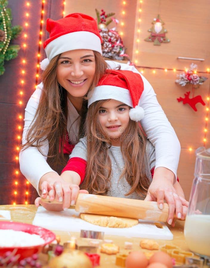 做圣诞节曲奇饼的愉快的家庭 免版税库存照片