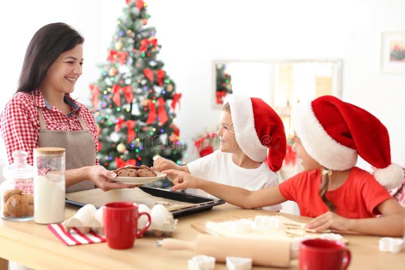 做圣诞节曲奇饼的母亲和孩子 免版税库存照片