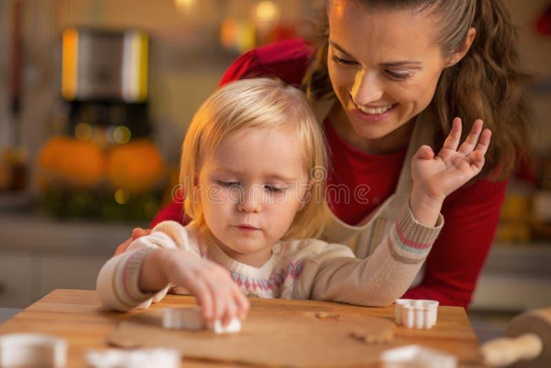 做圣诞节曲奇饼的母亲和婴孩 库存照片