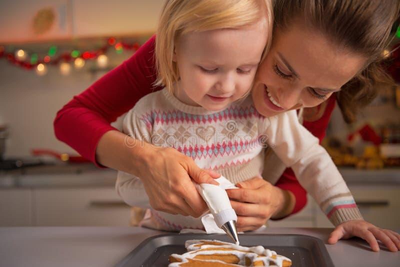 做圣诞节曲奇饼的母亲和婴孩 免版税库存照片