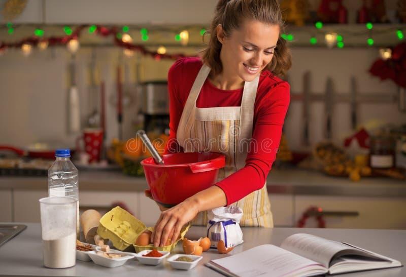 做圣诞节曲奇饼的主妇在厨房里 库存图片