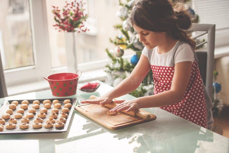 做圣诞节的美丽的小女孩自创曲奇饼 免版税图库摄影