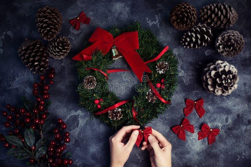 做圣诞节花圈平的位置的妇女 顶视图 Xmas车间 免版税库存照片