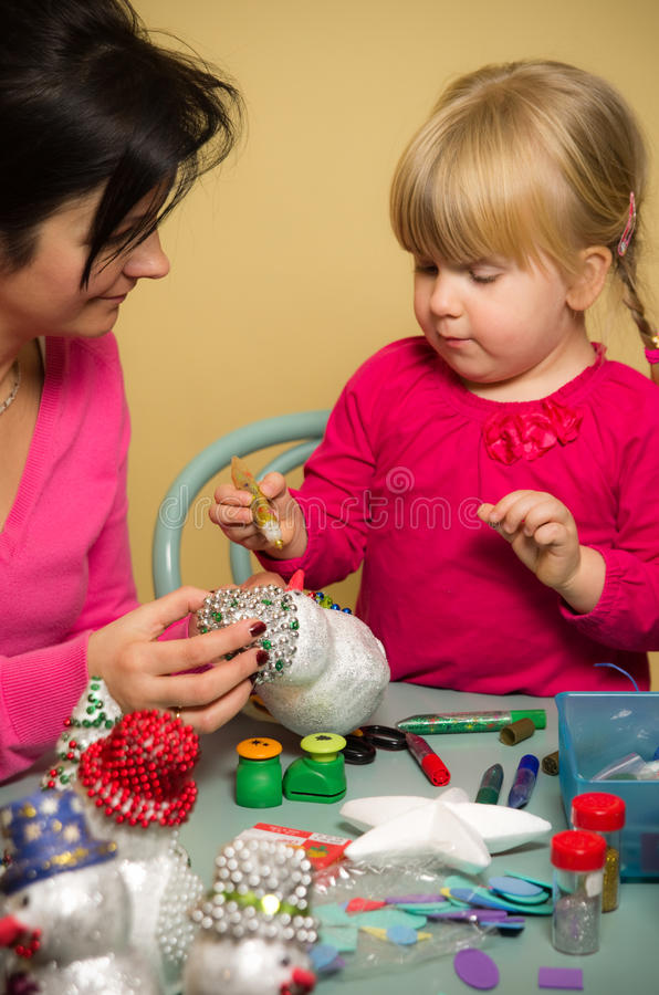 做圣诞节装饰的母亲和女儿 免版税库存图片