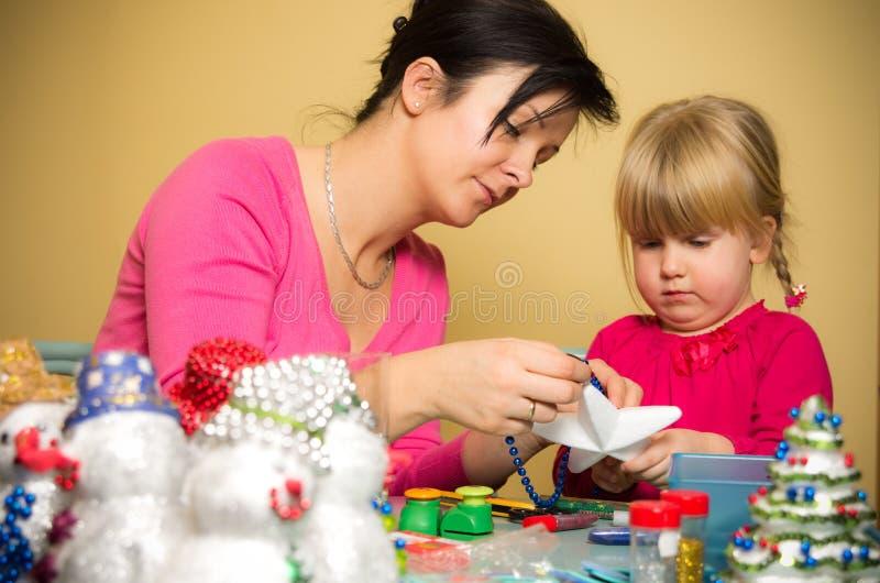 做圣诞节装饰的母亲和女儿 图库摄影