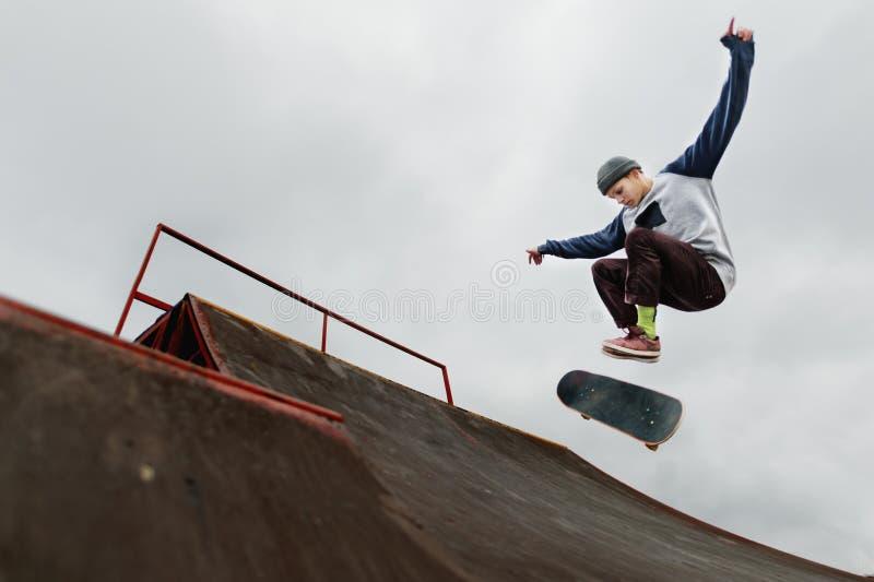 做在一个半管子的盖帽的少年溜冰板者一个把戏跃迁在多云天空背景 免版税库存照片