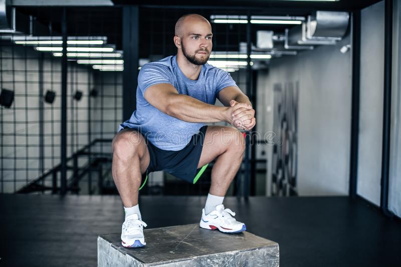 做在一个矮小箱子的运动员蹲坐在健身房 健身房的人制定出在一个木矮小箱子的身分 穿戴在体育单 免版税图库摄影
