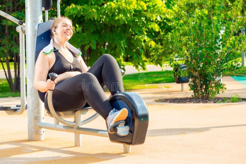 做在一辆固定式自行车的愉快和活跃过大的妇女锻炼 免版税库存照片