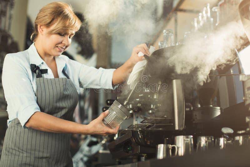 做在专业咖啡机器的老练的barista咖啡 免版税库存图片
