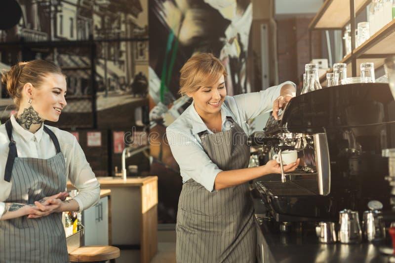 做在专业咖啡机器的老练的barista咖啡 库存图片