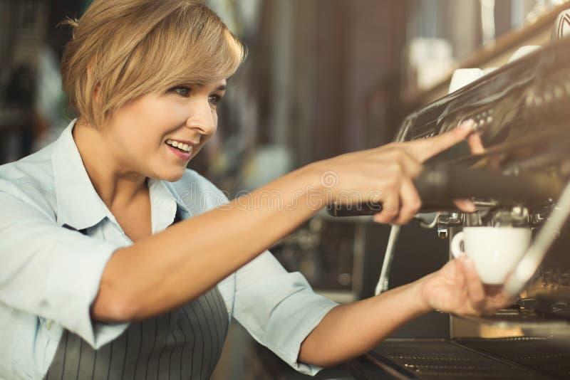 做在专业咖啡机器的老练的barista咖啡 免版税库存照片