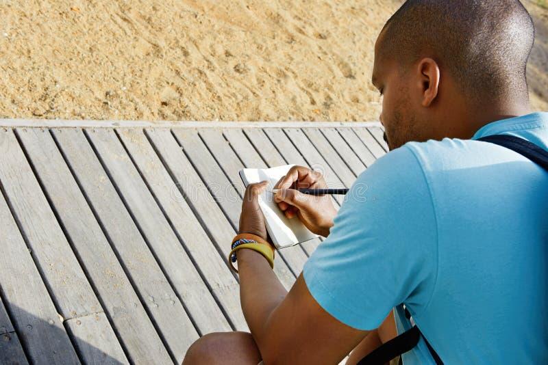做在习字簿的可爱的随便加工好的年轻美国非洲行家人笔记 学生为教训做准备在 库存照片