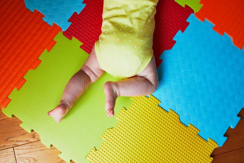 做在五颜六色的戏剧席子的婴孩肚子时间 库存图片