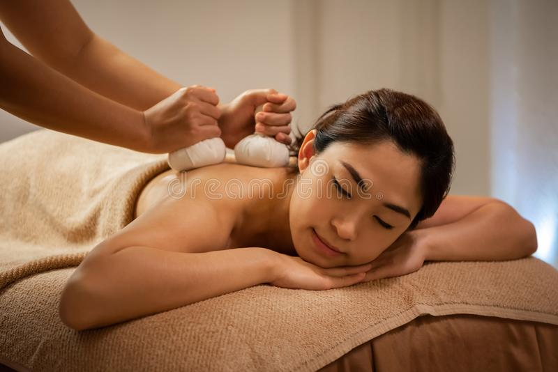 做在亚洲女性身体的女按摩师按摩在温泉沙龙 免版税库存图片