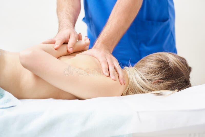 做在人的后面的生理治疗师愈合治疗 穿蓝色制服的治疗师 整骨疗法 按摩脊柱治疗者 库存图片