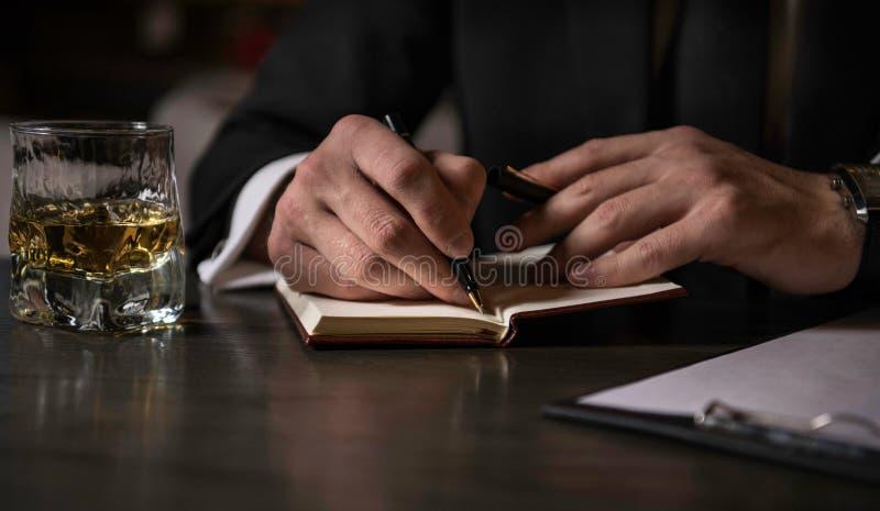 做在他的笔记本的商人的手的关闭笔记 免版税库存照片
