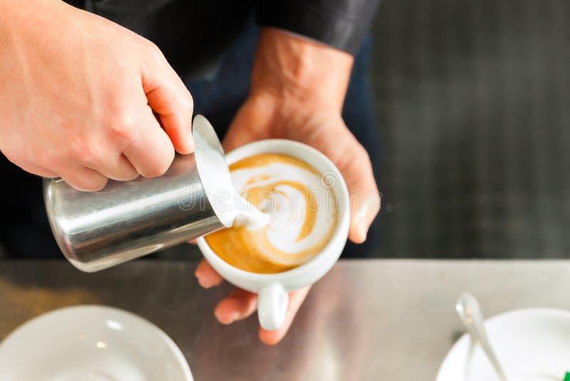 做在他的coffeeshop的Barista热奶咖啡 免版税库存图片