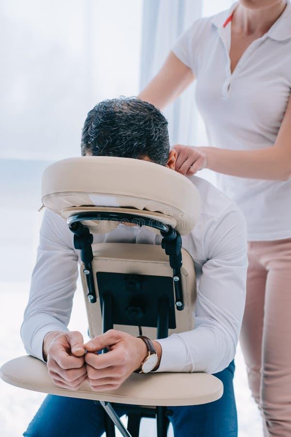 做在位子的女按摩师肩膀按摩 免版税库存图片