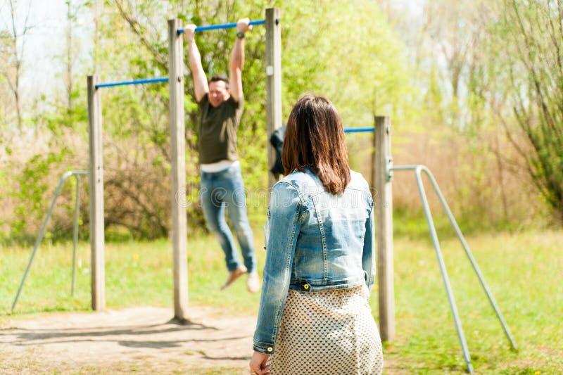 做在便装样式的年轻夫妇户外健身excercises 免版税库存图片