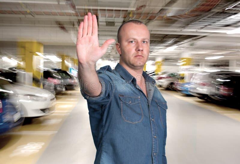 做在停车库的英俊的人中止姿态 免版税库存图片