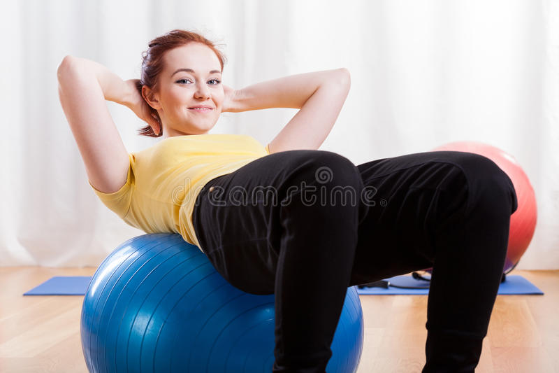 做在健身房球的女孩咬嚼 库存照片