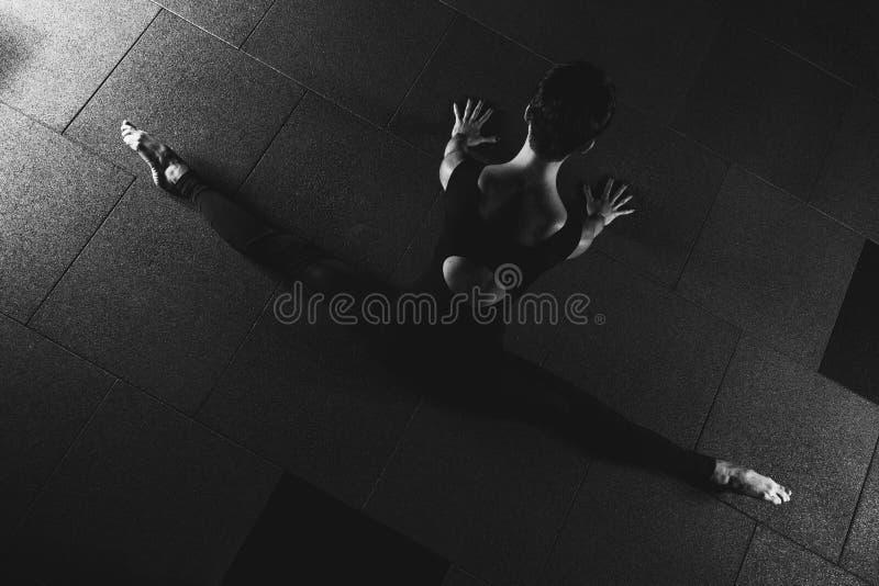 做在健身房瑜伽姿势的健身女孩分裂锻炼在黑暗的大厅里 免版税图库摄影