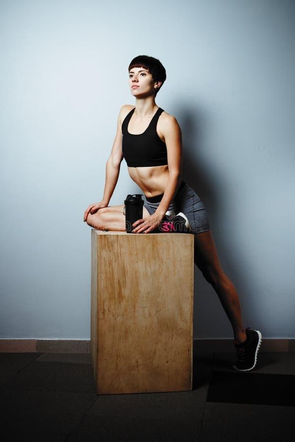 做在健身房瑜伽姿势的健身女孩锻炼在木的大厅里 库存图片