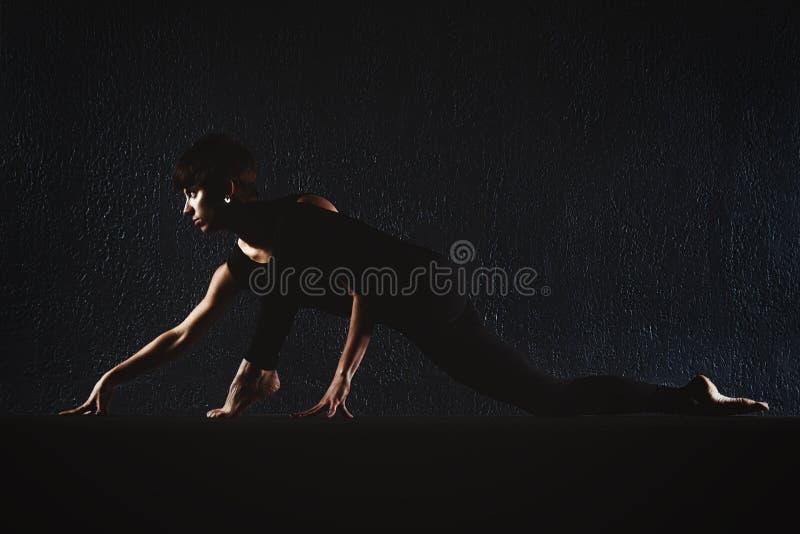 做在健身房瑜伽姿势的健身女孩锻炼在黑暗的大厅, spor里 库存图片