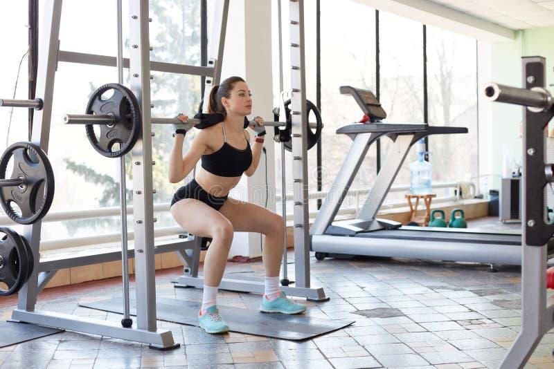 做在健身房的专业女运动员的图象锻炼,与杠铃的蹲坐,练习举重,开发力量和定义  库存图片