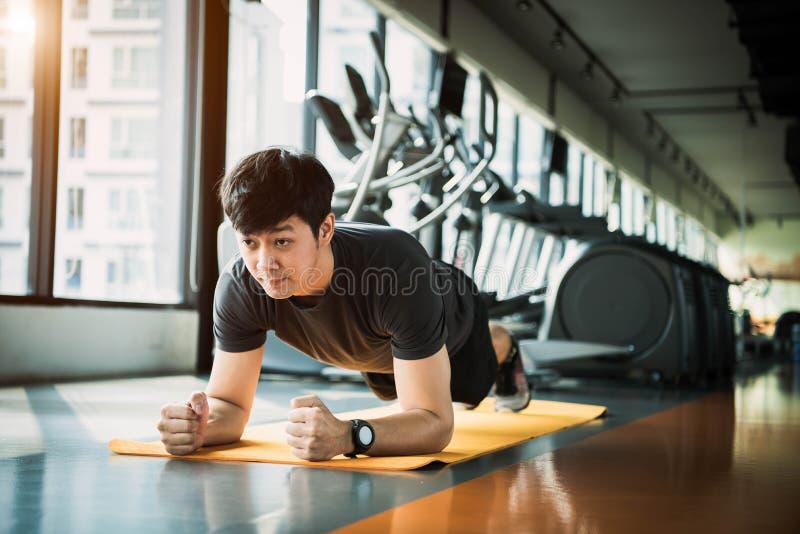 做在健身房的亚裔健身人画象铺板锻炼 人生活方式和体育锻炼概念 免版税库存图片