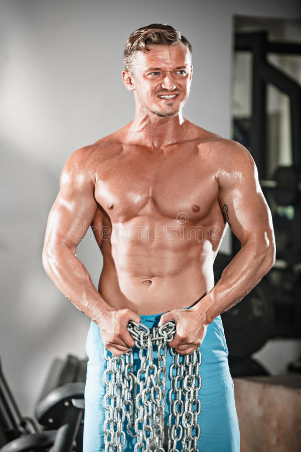 做在健身房的可爱的hunky黑人男性爱好健美者体型姿势与铁链子 库存图片