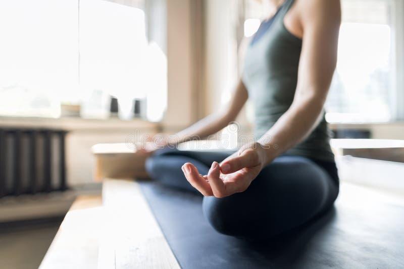 做在健身房的妇女瑜伽锻炼,特写镜头体育健身女孩坐的莲花姿势 库存照片